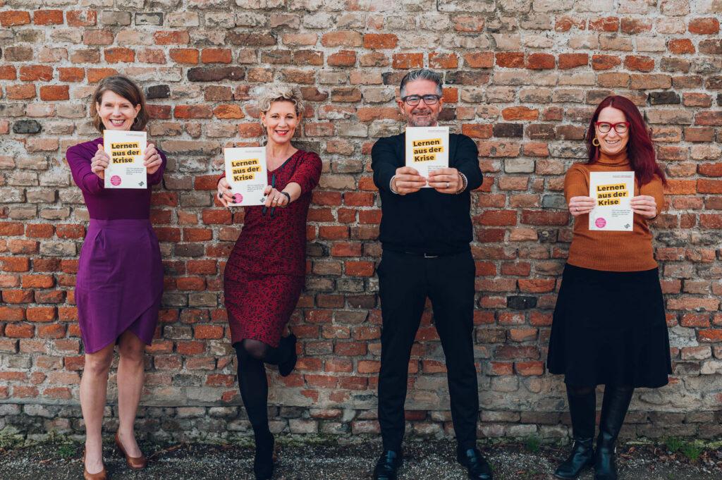 Vier Personen vor einer Wand mit dem neuen Praxisbuch Lernen aus der Krise